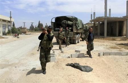 Soldiers loyal to the Syrian regime gesture in the village of Debaa near Qusair, after the Syrian army took control of the village from rebel fighters June 7, 2013. REUTERS/Rami Bleible