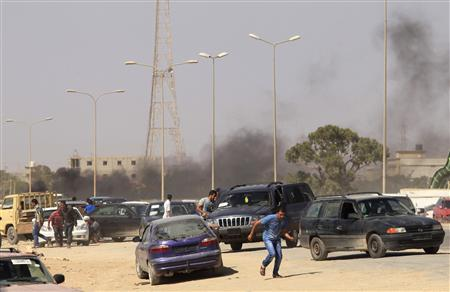 Protesters run after an attack on a Libyan militia, the Libya Shield brigade, headquarters in Benghazi, June 8, 2013. REUTERS/Esam Al-Fetori