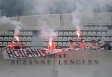 Seguranças tentam conter manifestantes durante a partida final do Aberto da França, em Paris. Os manifestantes, um deles empunhando sinalizadores, interromperam brevemente a partida dos espanhóis Rafael Nadal e David Ferrer neste domingo, vencida por Nadal. 09/06/2013 REUTERS/Stephane Mahe
