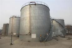 Мужчина спускается по лестнице нефтяного хранилища на НПЗ PetroChina в Ланьчжоу 7 января 2011 года. Потребление нефти и нефтепереработка в Китае снизились до минимума девяти месяцев в мае на фоне признаков замедления экономического роста. REUTERS/Stringer