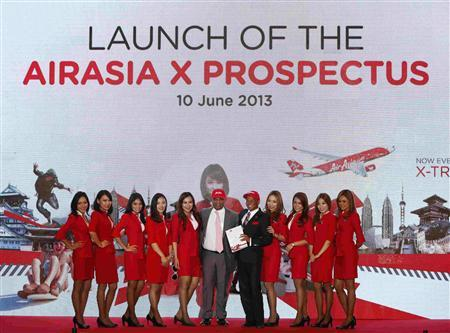 Tony Fernandes (C), founder of long-haul carrier AirAsia X, and Chief Executive Officer Azran Osman-Rani (5th R), hold a newly launched AirAsia X Prospectus as they pose with AirAsia X flight attendants during its launch ceremony in Kuala Lumpur June 10, 2013. REUTERS/Bazuki Muhammad