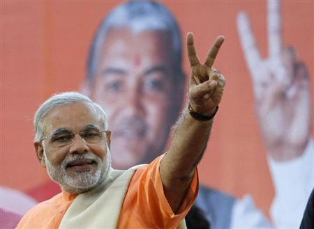 Narendra Modi, chief minister of Gujarat state, gestures on the podium during a felicitation ceremony outside the party office in Ahmedabad December 20, 2012. REUTERS/Amit Dave/Files