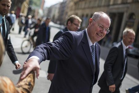 The top-candidate of the Social Democratic Party (SPD) in this year's German general election Peer Steinbrueck shakes hands with a passerby as he walks through central Leipzig after a ceremony marking the 150th anniversary of the foundation of Germany's social democratic party, May 23, 2013. REUTERS/Thomas Peter