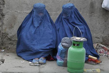 Afghan women sit along a street as they wait for transportation in Kabul March 19, 2013. REUTERS/Omar Sobhani