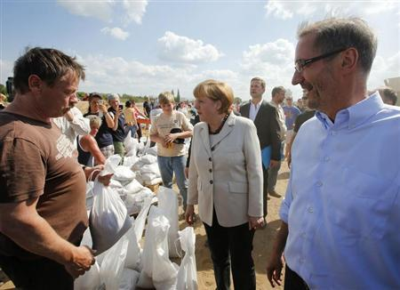 German Chancellor Angela Merkel and Brandenburg State Premier Matthias Platzeck (R) meet volunteers reinforcing a dyke at the bank of the river Elbe in the town of Wittenberge June 10, 2013. REUTERS/Fabrizio Bensch
