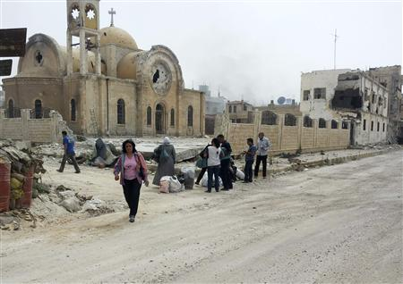 Residents walk near a damaged church as they are seen in Qusair to inspect their houses and collect their belongings June 8, 2013. REUTERS/Rami Bleibel