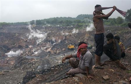 Workers sit atop of an open cast coal field at Dhanbad district in Jharkhand September 18, 2012. REUTERS/Ahmad Masood/Files