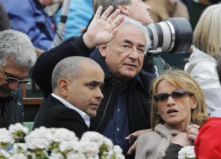 Former International Monetary Fund (IMF) chief Dominique Strauss-Kahn (C) and Myriam L'Aouffir (R) watch the men's singles final match between Rafael Nadal of Spain and compatriot David Ferrer at the French Open tennis tournament at the Roland Garros stadium in Paris June 9, 2013. REUTERS/Stephane Mahe