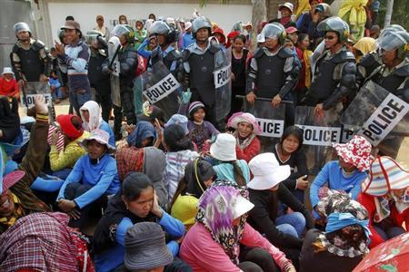 Garment workers sit beside police officers during a protest in front of a factory owned by Sabrina (Cambodia) Garment Manufacturing in Kampong Speu province, west of the capital Phnom Penh June 3, 2013. REUTERS/Samrang Pring
