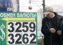Мужчина проходит мимо вывески пункта обмена валюты в Москве 15 января 2009 года. Рубль обновляет многомесячные минимумы на торгах вторника, следуя в русле общих негативных тенденций валют развивающихся и сырьевых рынков, которые распродаются из-за рисков сокращения стимулирующих программ крупнейших центробанков, а также на фоне ухудшения показателей китайской экономики, что чревато снижением спроса на сырье. REUTERS/Sergie Karpukhin