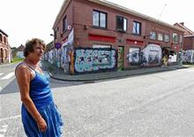 Frie Lauwers, who lives in the Belgian village of Doel, stands next to an abandoned building in Doel June 5, 2013. REUTERS/Yves Herman
