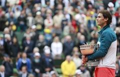 Espanhol Rafael Nadal ouve o hino nacional de seu país após vencer o torneio Aberto da França, em Paris. Rafael Nadal ainda se vê muito distante do recorde de 17 títulos individuais de Grand Slam conquistados por seu rival Roger Federer, embora o espanhol tenha apenas 27 anos e já acumule 12 troféus dos torneios mais importantes do mundo. 9/06/2013. REUTERS/Vincent Kessler