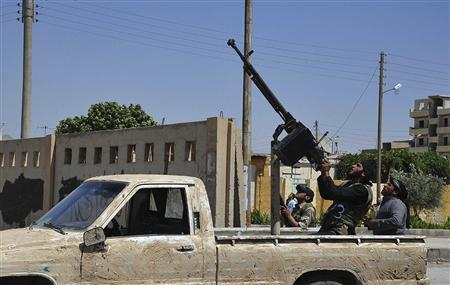 A member of the Free Syrian Army aims his machine gun mounted on a pick-up truck in Raqqa province, eastern Syria June 10, 2013. REUTERS/Nour Fourat