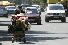 Женщина везет коляску с товарами для продажи по улице Тбилиси 4 июня 2013 года. Грузии необходимо сократить политическую неопределенность в стране и вступить в более активный диалог с инвесторами для прекращения экономического спада, сказал представитель Международного валютного фонда (МВФ). REUTERS/David Mdzinarishvili