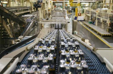 Bottles of soft drinks made by drinks company Britvic sit on a conveyor belt at Britvic's bottling plant in London March 25, 2009. REUTERS/Luke MacGregor