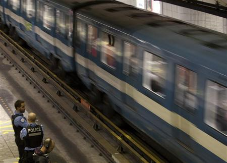 Police officers watch a train pass in a subway station in Montreal, May 10, 2012. REUTERS/Olivier Jean