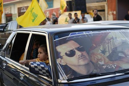 An image of Syria's President Bashar al-Assad is seen on a car's windscreen as Hezbollah supporters celebrate, after the Syrian army took control of Qusair from rebel fighters, in the Shi'ite town of Hermel June 5, 2013. REUTERS/Jamal Saidi