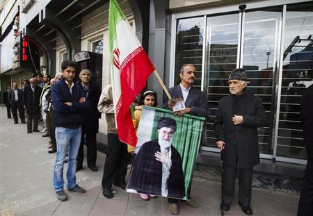 A man holds an Iranian flag and picture of Iran's Supreme Leader Ayatollah Ali Khamenei as he stands in the line to cast his vote during the parliamentary election, at a mosque in eastern Tehran March 2, 2012. REUTERS/Raheb Homavandi/Files