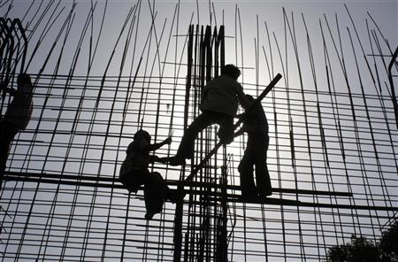 Labourers work at a riverfront construction site near the Sabarmati river in Ahmedabad June 17, 2009. REUTERS/Amit Dave/Files