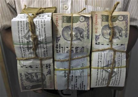 An employee carries bundles of Indian currency notes inside a bank in Agartala, capital of India's northeastern state of Tripura, October 26, 2009. REUTERS/Jayanta Dey/Files