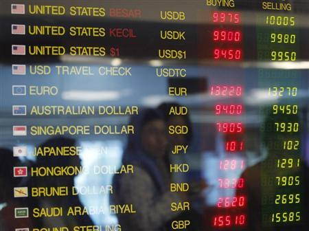 A woman is reflected in an electronic board as she looks at exchange rates of foreign currencies against the Indonesian rupiah at a money changer in Jakarta June 11, 2013. REUTERS/Enny Nuraheni
