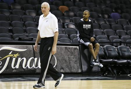 San Antonio Spurs Tony Parker (R) watches other players during practice for their NBA Finals basketball playoff series against the Miami Heat, as coach Gregg Popovich walks by, in San Antonio, Texas June 12, 2013. REUTERS/Lucy Nicholson
