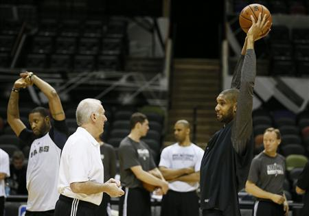 San Antonio Spurs coach Gregg Popovich (2nd L) speaks with player Tim Duncan (R) as teammate Tracy McGrady (L) warms up during practice for their NBA Finals basketball playoff series against the Miami Heat in San Antonio, Texas June 12, 2013. REUTERS/Lucy Nicholson