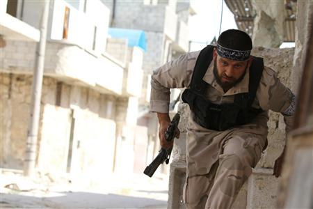 A Free Syrian Army fighter runs for cover near Nairab military airport in Aleppo June 12, 2013.REUTERS/Hamid Khatib