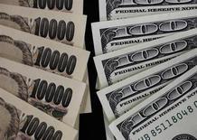 Купюры валют доллар СШа и иена в Токио 2 августа 2011 года. Доллар снизился до минимума десяти недель к иене, так как инвесторы продолжают опасаться сокращения проводимой ФРС программы скупки облигаций. REUTERS/Yuriko Nakao