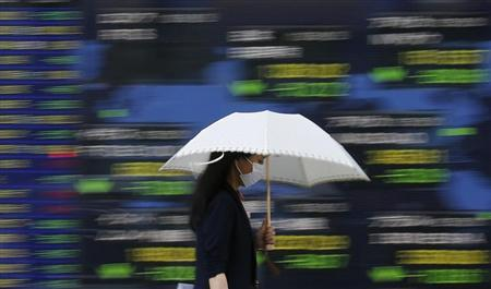A woman carrying an umbrella walks past a stock quotation board outside a brokerage in Tokyo June 3, 2013. REUTERS/Toru Hanai