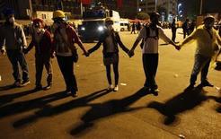 Демонстранты в живой цепи на площади Таксим в Стамбуле 12 июня 2013 года. Сотни недовольных правительством Тайипа Эрдогана собрались на стамбульской площади Таксим утром в четверг, несмотря на то, что накануне крупные силы полиции ликвидировали на этом месте лагерь демонстрантов. REUTERS/Murad Sezer