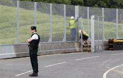 A Police Service of Northern Ireland officer guards the road to the Lough Erne Golf Resort where the G8 summit will be held next week, in County Fermanagh June 10, 2013. REUTERS/Cathal McNaughton