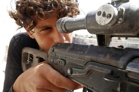 A Free Syrian Army fighter points his weapon near Kindi hospital, which is under the control of forces loyal to President Bashar Al-Assad, as both sides fight to take control of the hospital in Aleppo June 11, 2013. REUTERS/Hamid Khatib