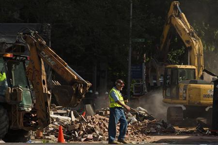 A construction worker walks near the debris following a building collapse in Philadelphia June 5, 2013. REUTERS/Eduardo Munoz