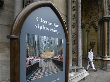 A woman walks outside Westminster Abbey which was closed after a man defaced a painting of Britain's Queen Elizabeth hanging inside in London, June 13, 2013. REUTERS/Paul Hackett
