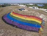 "Landscape ""artists"" put finishing touches on a giant rainbow flag on the top of a dormant landfill, nicknamed Mount Trashmore, in Key West, Florida, June 4, 2010. REUTERS/Andy Newman"