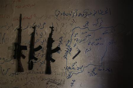 Three weapons hang on a wall depicting a map of Syria in a safe house of Martyr Al-Abbas, a rebel group, in Aleppo June 11, 2013. REUTERS/Muzaffar Salman