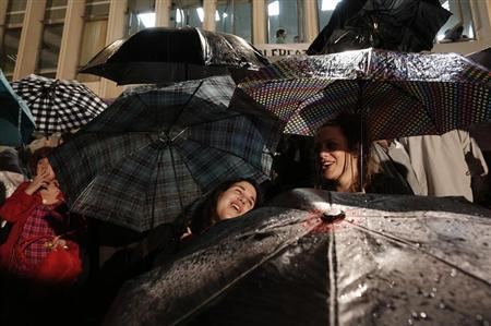 Protesters hold umbrellas as they stand in heavy rain outside Greek state television ERT headquarters in Athens June 12, 2013. REUTERS/John Kolesidis