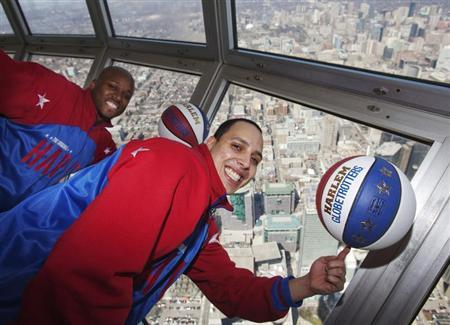 Members of the exhibition basketball team Harlem Globetrotters Moo Moo Evans and Blenda Rodriguez (R) pose at the top of the CN tower in Toronto, April 1, 2010. REUTERS/Mark Blinch