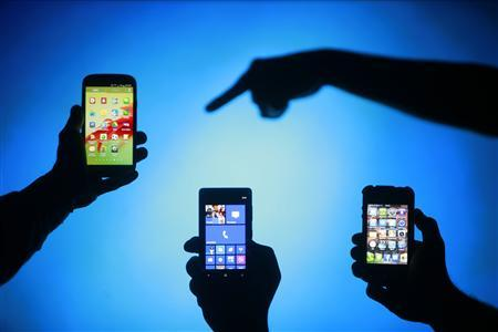 Men are silhouetted against a video screen as they pose with Samsung Galaxy S3, Nokia Lumia 820 and iPhone 4 smartphones (L-R) in this photo illustration taken in the central Bosnian town of Zenica, in this May 17, 2013 file photo. REUTERS/Dado Ruvic/Files