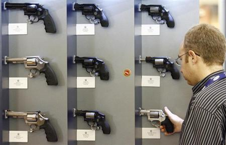 A visitor looks at a Smith & Wesson gun at MILIPOL International State Security Exhibition in Paris October 9, 2007. REUTERS/Regis Duvignau