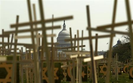 With the U.S. Capitol in the background, crosses symbolizing grave markers are placed upon the National Mall in Washington April 11, 2013. REUTERS/Kevin Lamarque
