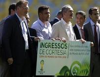 O secretário-geral da Fifa, Jérôme Valcke (E), o ex-jogador Ronaldo e o ministro do Esporte, Aldo Rebelo, seguram cartaz representando ingresso da Copa do Mundo. A entidade está preocupada com os problemas para retirada de ingressos na Copa das Confederações e também para o Mundial. Foto de 15/5/2013 REUTERS/Ricardo Moraes