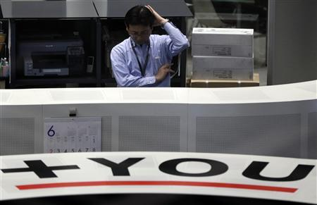 An employee of the Tokyo Stock Exchange (TSE) works at the bourse in Tokyo June 13, 2013. REUTERS/Toru Hanai