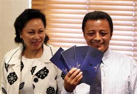 Former Madagascar leader Marc Ravalomanana (R) holds up air tickets standing beside his wife Lalao during a media briefing in Johannesburg January 20, 2012. REUTERS/Siphiwe Sibeko