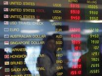 Женщина отражается в электронном табло пункта обмена валюты в Джакарте 11 июня 2013 года. Доллар растет с минимума четырех месяцев, но, скорее всего, подешевеет к валютной корзине четвертую неделю подряд. REUTERS/Enny Nuraheni