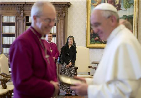 Pope Francis (R) exchange gifts with the Archbishop of Canterbury Justin Welby, in front of his wife Caroline (C) looks at then during a private audience at the Vatican June 14, 2013. REUTERS/Alessandra Tarantino/Pool