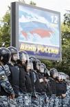 Полицейские стоят на пути оппозиционной колонны на уличной акции в Москве 12 июня 2013 года. Владимир Путин, велевший правительству увеличить ассигнования на социальные нужды, сказал, что не сбросил со счетов любимую левыми идею отказа от единого 13-процентного подоходного налога, хотя плоская шкала и помогла выводу бизнеса из тени. REUTERS/Sergei Karpukhin