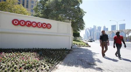 Men look at the logo of Qatar Telecom Ooredoo, formerly Qatar Telecom Qtel, as they walk past the company's head office in Doha March 16, 2013. REUTERS/Fadi Al-Assaad