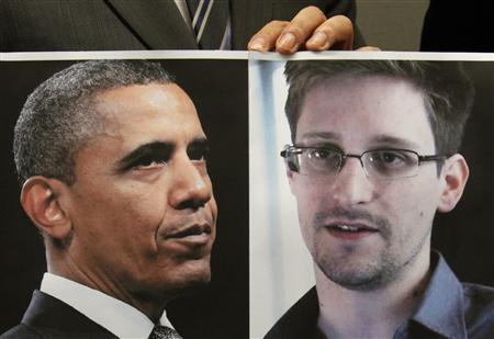 Pro-democracy lawamaker Gary Fan holds a combination photo featuring U.S. President Barack Obama (L) and Edward Snowden, a contractor at the National Security Agency (NSA), during a news conference in Hong Kong, in support of Snowden, June 14, 2013. REUTERS/Bobby Yip
